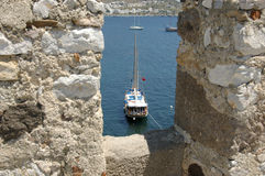 Through the turrets to the sea. A ship on the sea seen between the turrets on Bodrum Castle in Turkey which dates back to the crusades Royalty Free Stock Photo