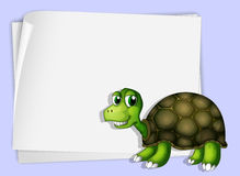 A turtle beside an empty paper Stock Photography