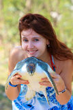 At the turtle farm. Young woman holding a sea turtle out of the water Stock Photos