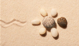 Turtle made of sea stones with mark of tail on sand Stock Photo