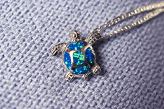 Turtle pendant. Turtle shaped silver medallion with an opal boulder stock photography