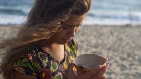 Turtle sanctuary. Portrait of young women in sun light looking on turtle in our hand,worry face, hair flapping on the wind, turtle  sanctuary hatchery located on stock video