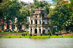 Turtle Tower at Hoan Kiem Lake in Hanoi, Vietnam. Hanoi, Vietnam. Turtle Tower at Hoan Kiem Lake in Hanoi, Vietnam. Tree at the foreground, cloudy moody weather stock photo