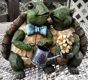 Turtles. The photo is of a ceramic figurine or statue of two turtles with a watering can Stock Images