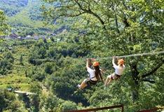 Turyści krzyżują długą ścieżkę przez lasu przez rzeczną tiarę i góry wagonem kolei linowej obraz royalty free