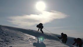 Turyści wspina się halną śnieżną falezę Rozciągać pomocną dłoń ludzie pomagają each inny Praca zespołowa, pracy zespołowej pojęci zdjęcie wideo