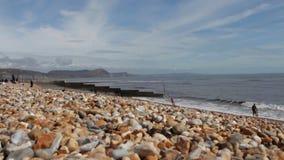 Turyści chodzą na Brytyjskiej otoczak plaży na pogodnym wiosna dniu zbiory