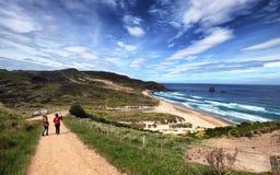 Turyści chodzi w kierunku Sandfly zatoki wyrzucać na brzeg przy Otago, Nowa Zelandia obraz royalty free