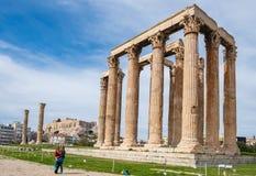 Turyści fotografuje przed Grecką świątynią Olimpijski Zeus z akropolem Ateny w tle zdjęcia royalty free