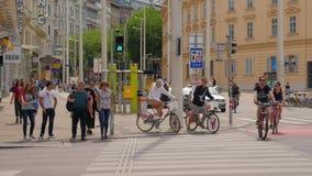 Turyści i cykliści czekają zielonego sygnał przy miasta crosswalk i wtedy krzyżują drogę zbiory