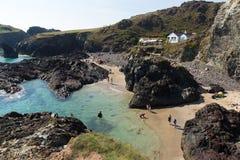 Turyści i wczasowiczki cieszy się późnego lata światło słoneczne przy Kynance zatoczki plażą jaszczurka Cornwall Anglia UK Fotografia Royalty Free