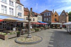Turyści je mussels i francuzów dłoniaki w restauracjach nie daleko od Targowego kwadrata Bruges Fotografia Stock