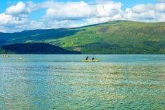 Turyści na czółnie na spokojnym błękitnym Loch Lomond jeziorze w Luss, Szkocja, 21 Lipiec, 2016 Zdjęcie Stock