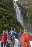 Turyści na pływa statkiem łodzi zbliża się Stirling Spadają, Milford dźwięk, Fiordland, Południowa wyspa Nowa Zelandia Zdjęcie Royalty Free