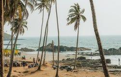 Turyści ogląda ocean wyrzucać na brzeg z drzewkami palmowymi, wokoło niektóre plenerową kawiarnią i Zdjęcia Royalty Free