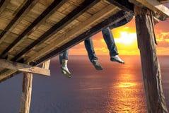 Turyści siedzi nogi wiesza na drewnianym tarasie cieszą się z oceanem fotografia royalty free