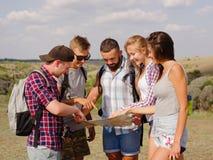 Turyści target371_0_ przy mapę Prowadzi pokazywać mapę podróżni ucznie na naturalnym tle Fachowy wycieczkuje pojęcie Zdjęcia Stock
