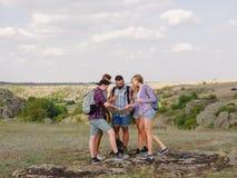Turyści target371_0_ przy mapę Przewdonika seansu mapa na naturalnym tle pomocy tła plecaka kompasu pojęcia wyposażenie najpierw  Zdjęcie Royalty Free