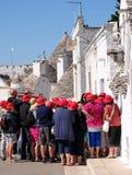 Turyści w Puglian miasteczku patrzeje i fotografuje tradycyjnych suchego kamienia trulli domy które są unikalni Alberobello, obrazy royalty free