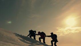 Turyści wspina się halną śnieżną falezę Rozciągać pomocną dłoń ludzie pomagają each inny Praca zespołowa, pracy zespołowej pojęci zbiory wideo