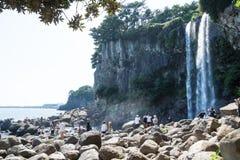 Turyści wspina się na kamieniach przy Jeongbang siklawą w Seogwipo, Jeju wyspa, Południowy Korea zdjęcia royalty free
