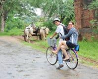 Turyści jedzie rower na wiejskiej drodze w Bagan, Myanmar Zdjęcia Royalty Free