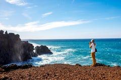 Turysta fotografuje powulkanicznego wybrzeże na Lanzarote wyspie w Hiszpania Zdjęcie Stock
