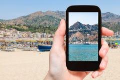turysta fotografuje Taormina miasto na przylądku w Włochy fotografia royalty free