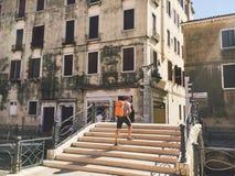 Turysta iść widok z jego plecy Wenecja, Włochy z pomarańczową kamerą na jego szyi wzdłuż starych ulic i plecakiem obraz stock