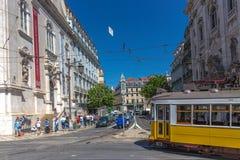 Turysta i miejscowi jedzie tradycyjnego żółtego tramwaj w w centrum Lisbon w pięknym niebieskim niebie, Lisbon, Portugalia, Maj - zdjęcie royalty free