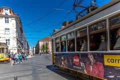 Turysta i miejscowi jedzie tradycyjnego żółtego tramwaj w w centrum Lisbon w pięknym niebieskim niebie, Lisbon, Portugalia, Maj - obrazy stock