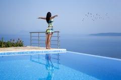 Turysta na nieskończoność basenie z szeroko rozpościerać rękami Fotografia Royalty Free