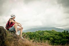 Turysta relaksuje na rockowy i cieszy się podziwiać z plecakiem Fotografia Royalty Free
