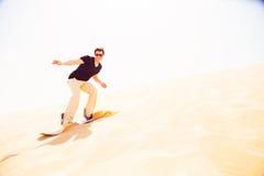 Turysta Sandboarding W pustyni Obrazy Royalty Free