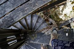 Turysta w butach chodzi na starym drewnianym ślimakowatym schody zdjęcia royalty free