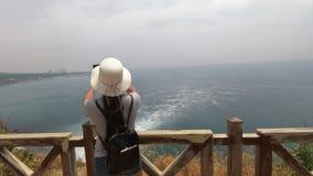 Turysta w kapeluszu bierze wideo niekończący się morze i szybka siklawa pi?kny widok zbiory wideo