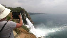 Turysta w kapeluszu cieszy się pięknego widok, także bierze obrazki ono na pastylce, i siklawa i morze zbiory wideo