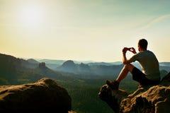 Turysta w popielatej koszulce bierze fotografie z mądrze telefonem na szczycie skała Marzycielski górkowaty krajobraz below, poma Zdjęcia Stock