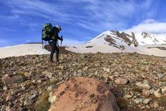 Turysta wspina się skalistego skłon góra nakrywający szczyt fotografia stock