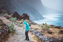 Turysta wycieczkuje od Cruzina Ponta w hoodie w Aranhas dolinie robi zolowi Ogromne góry linia brzegowa i stary miejscowego kamie Zdjęcie Royalty Free