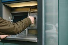 Turysta wycofuje pieniądze od ATM dla dalszy podróży Chwyta kartę od ATM Finanse, kredytowa karta, wycofanie Obrazy Royalty Free