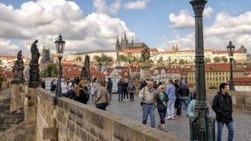 Turysta wypełniający Charles most z nim jest sławnymi rzeźbami z Praga kasztelem w tle, Praga, republika czech fotografia royalty free