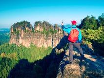 Turysta z czerwonym plecakiem bierze fotografie z telefonem skały i dolina Fotografia Stock