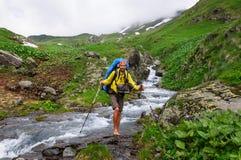Turysta z dużym plecak rzeki brodu skrzyżowaniem obrazy royalty free