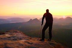 Turysta z medycyny szczudłem na halnym szczycie Zgłębia mglistą dolinną bellow sylwetkę ma Zdjęcia Royalty Free