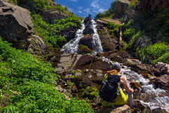 Turysta z plecaka obsiadaniem siklawą w górach Zdjęcia Royalty Free