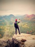 Turysta z plecaka stayon falezą i bierze fotografie z mądrze telefonem dżdżysta dolina Obrazy Royalty Free