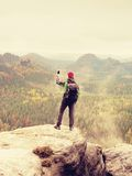 Turysta z plecaka stayon falezą i bierze fotografie z mądrze telefonem dżdżysta dolina Fotografia Stock
