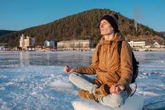 Turysta z plecakiem medytuje obsiadanie w Lotosowej pozycji na lodzie jeziorny Baikal zdjęcia stock