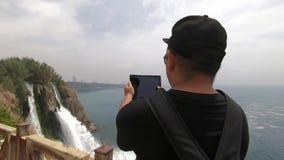 Turysta z plecakiem na jego z powrotem blisko stromego skłonu i wp8lywy wideo piękna siklawa zdjęcie wideo